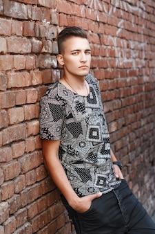 Hipster młody facet w czarnej koszuli stojący w pobliżu ściany z czerwonej cegły z graffiti