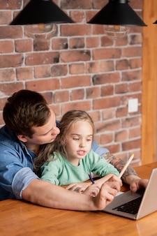 Hipster młody ojciec z tatuażem na ramieniu siedzi przy stole z córką i za pomocą laptopa, pomagając jej przygotować się do szkolnego egzaminu