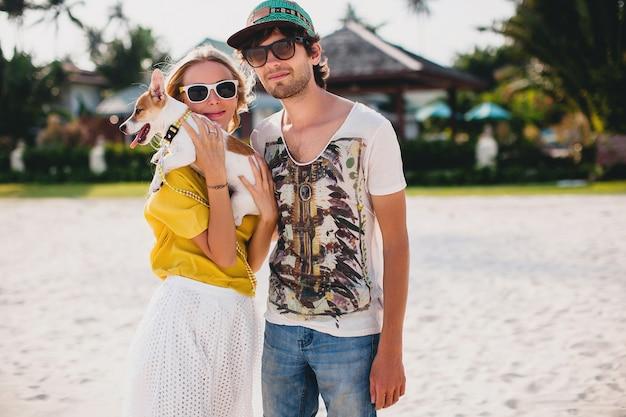 Hipster młody stylowy hipster zakochana para spacerująca grająca psa szczeniaka jack russell na tropikalnej plaży, biały piasek, fajny strój, romantyczny nastrój, zabawa, słonecznie, mężczyzna kobieta razem, wakacje