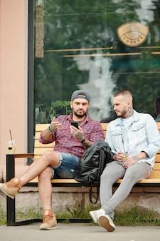 Hipster młodzi mężczyźni siedzący na ławce w pobliżu kawiarni i omawiający wiadomości internetowe