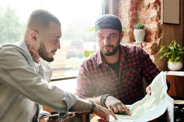 Hipster młodzi mężczyźni siedzący w przytulnej kawiarni i wskazujący na papierową mapę, omawiając podróż samochodem