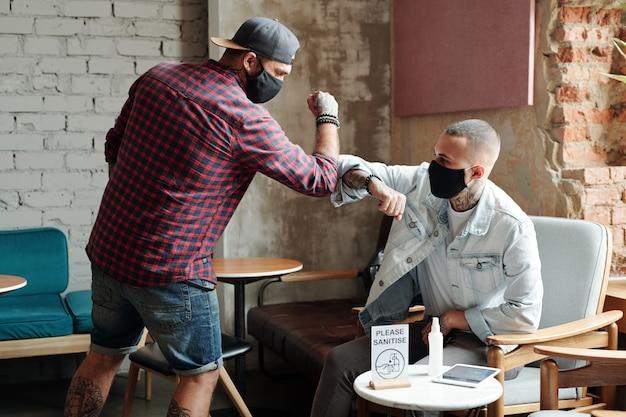 Hipster młodzi przyjaciele w maskach dotykają łokci zamiast uścisku dłoni podczas spotkania w lobby koronawirusa