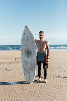 Hipster modny surfer na plaży z deską surfingową