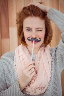 Hipster nosi sztuczne wąsy
