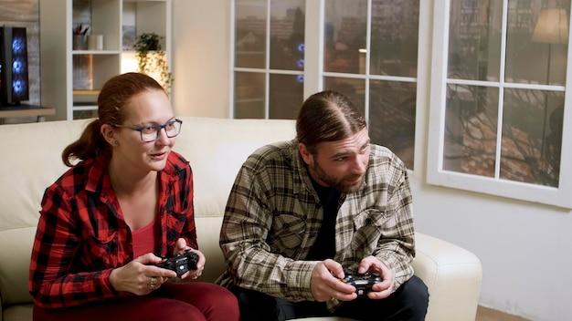 Hipster para siedzi na kanapie, grając w gry wideo za pomocą kontrolera bezprzewodowego. mężczyzna i kobieta przybijają piątkę.