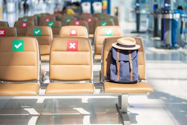 Hipster plecak i czapka na krześle na międzynarodowym lotnisku. nowe koncepcje normalne, bańka podróżna i dystansowanie społeczne, ochrona przed zakażeniem koronawirusem (covid-19)