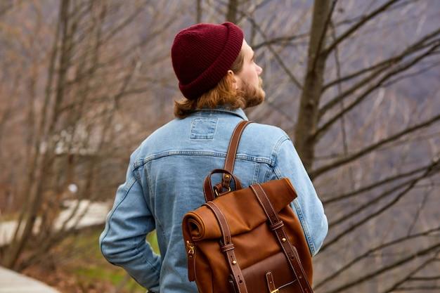 Hipster podróżnik cieszący się naturalnym otoczeniem stoi w kontemplacji mężczyzna w dżinsowej kurtce z l...
