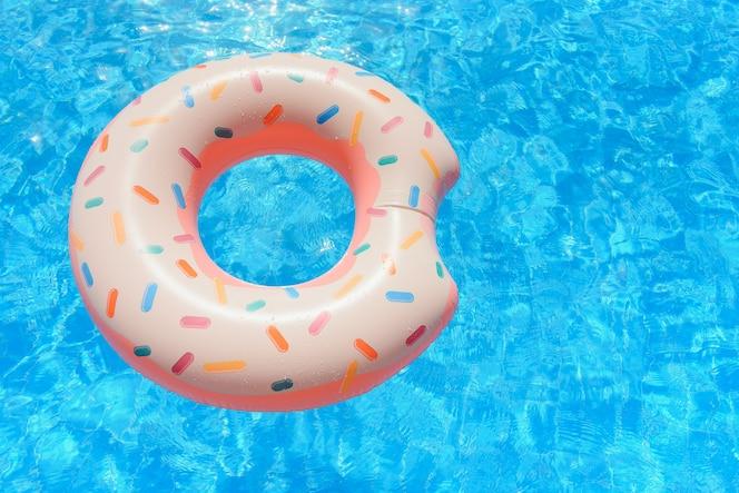Hipster posypany pączek unosi się w słonecznym tle basenu prosto w jasną, czystą wodę w basenie