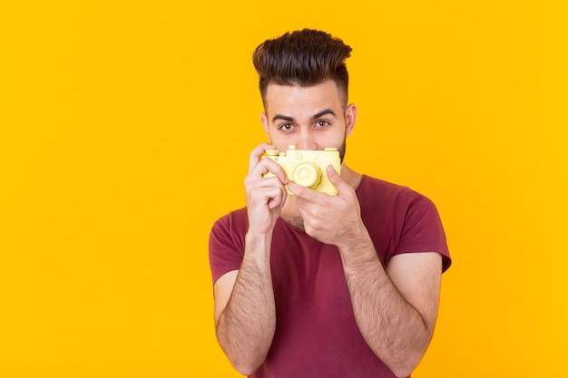 Hipster pozytywny młody człowiek z brodą, trzymając żółty aparat vintage, pozowanie na żółto
