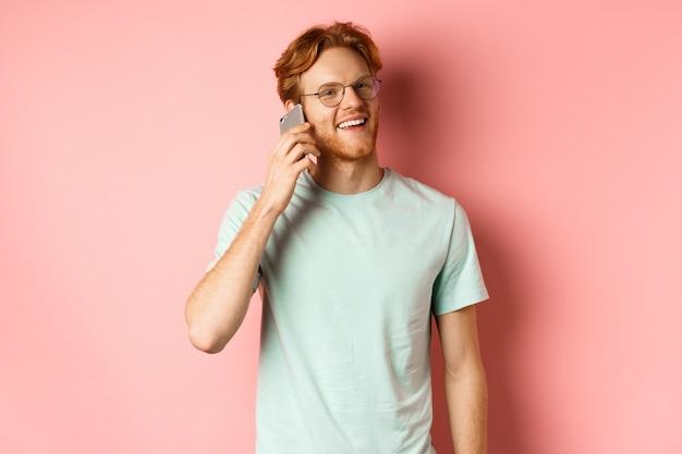 Hipster przystojny facet z rudymi włosami i brodą rozmawia przez telefon komórkowy, dzwoni do kogoś i wygląda szczęśliwy, stojąc na różowym tle.