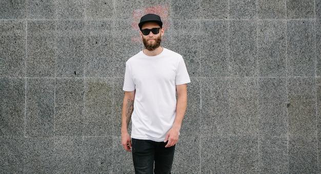 Hipster przystojny mężczyzna z brodą, ubrany w białą pustą koszulkę i czapkę z daszkiem z miejscem na logo lub projekt w swobodnym miejskim stylu