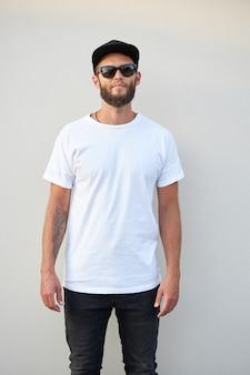 Hipster przystojny model męski z brodą ubrany w białą pustą koszulkę i czapkę z daszkiem z miejscem na twoje logo lub projekt w swobodnym miejskim stylu