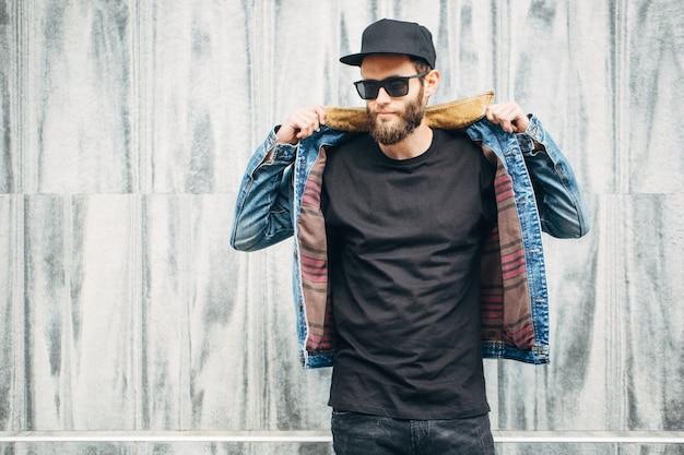 Hipster przystojny model męski z brodą w czarnej pustej koszulce z miejscem na twoje logo lub projekt w swobodnym miejskim stylu