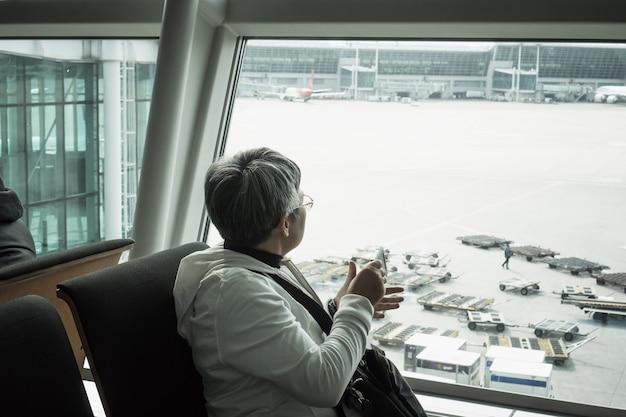 Hipster starsza podróżująca kobieta czekająca na lotnisku incheon największe lotnisko w korei południowej