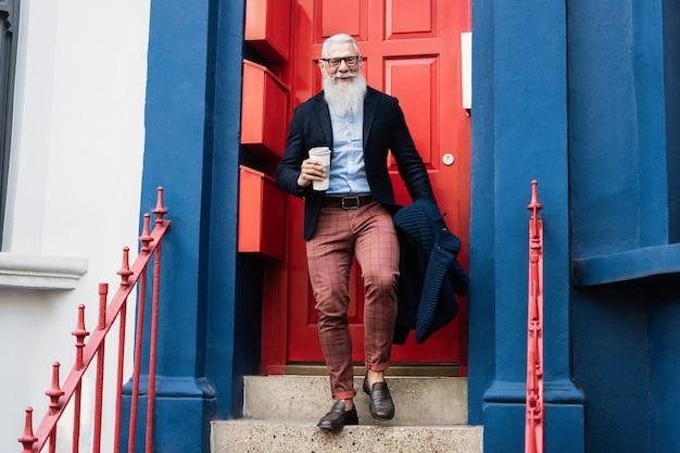 Hipster starszy mężczyzna pije kawę wychodząc z domu