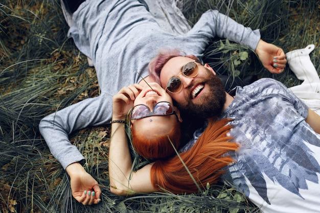 Hipster szczęścia para, w okulary przeciwsłoneczne, rudowłosa kobieta i brodaty mężczyzna, siedzący na zielonej trawie.