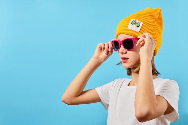 Hipster teen dziewczyna w okularach na sobie koszulę z dzianiny kapelusz patrząc z boku na niebieskim tle
