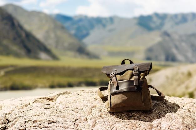 Hipster turystyczny brązowy plecak w górach, niewyraźny krajobraz. koncepcja podróży i wakacji