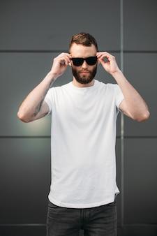 Hipster ubrany w biały pusty t-shirt i czapkę z daszkiem z miejscem na twoje logo