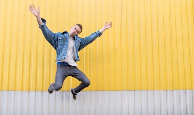 Hipster w dżinsowej kurtce skacze na tle jasnożółtej ściany.