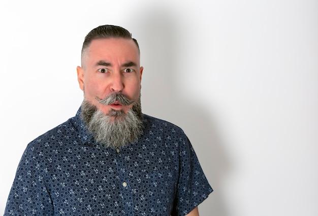 Hipster w koszuli kwiaty, duża broda i wąsy z bliska z zaskoczoną twarzą na białym