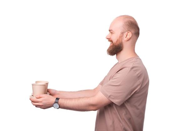 Hipster wesoły brodaty mężczyzna daje komuś dwa papierowe kubki kawy