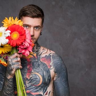 Hipster wytatuowany młody człowiek trzyma kolorowe kwiaty gerbera w ręku stojąc na szarym tle