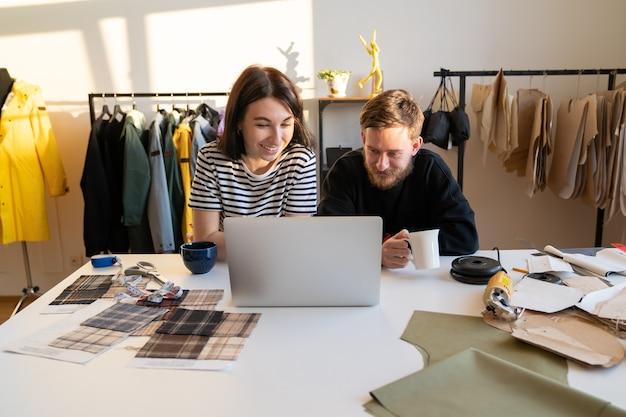 Hipsterscy projektanci pracują na laptopie z wykrojami ubrań w zespole krawieckim atelier w studio