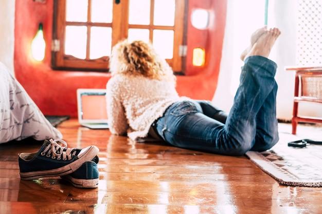 Hipsterska pani położyła się na podłodze w domu, pracując lub robiąc nowoczesne zakupy z laptopem podłączonym do internetu