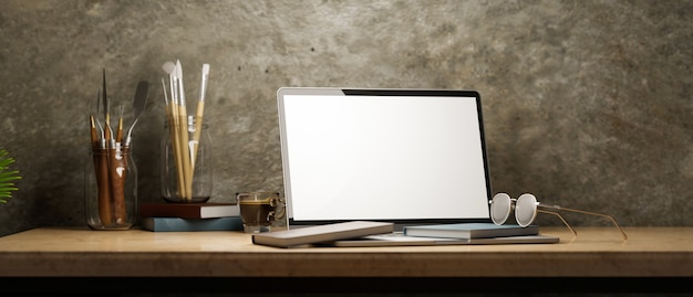 Hipsterski artysta przestrzeń robocza z laptopem pusty ekran makieta narzędzia do malowania na drewnianej ścianie na poddaszu