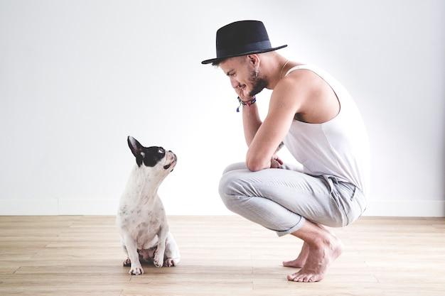 Hipsterski chłopiec w kapeluszu rozmawiający ze swoim francuskim psem buldogiem