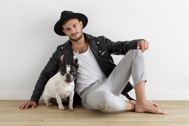 Hipsterski chłopiec w skórzanej kurtce i kapeluszu obok swojego zwierzaka, buldoga francuskiego na białym tle