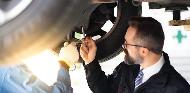 Hipsterski żłóbek z brodą i schowkiem z listą kontrolną porozmawiaj z doświadczonym mechanikiem pracującym pod pojazdem w serwisie samochodowym. opieka samochodowa i koncepcja warsztatu samochodowego.