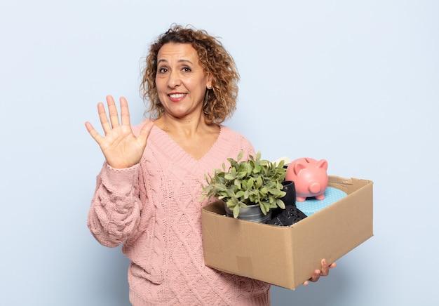 Hispanic kobieta w średnim wieku, uśmiechnięta i wyglądająca przyjaźnie, pokazująca numer pięć lub piąty z ręką do przodu, odliczający w dół