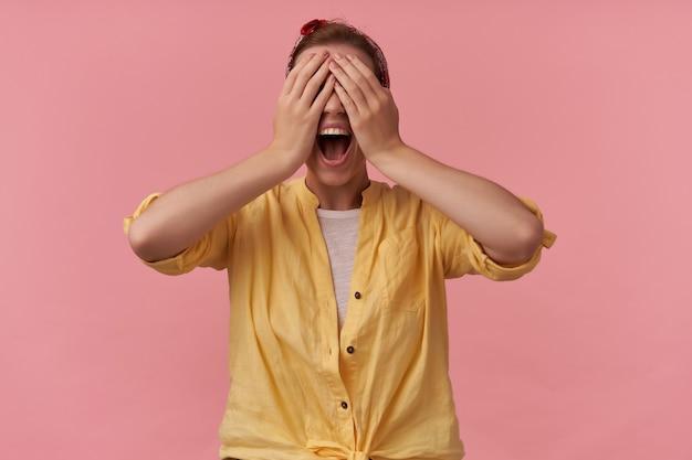 Histeryczna wściekła młoda kobieta w żółtej koszuli z opaską na głowie zakryła oczy rękami i krzyczała nad różową ścianą