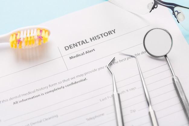 Historia dentystyczna z profesjonalnymi stalowymi instrumentami dentystycznymi, lustrem w pobliżu szczoteczki do zębów i okularami.
