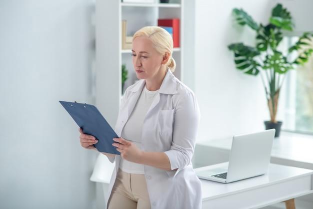 Historia medyczna. blondynka lekarz w średnim wieku trzyma dokumenty i czyta
