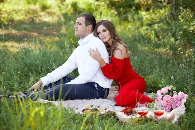 Historia miłosna kochającej się pary mężczyzn i kobiet na wiosnę na łonie natury w lesie. para uścisków, piknik w parku