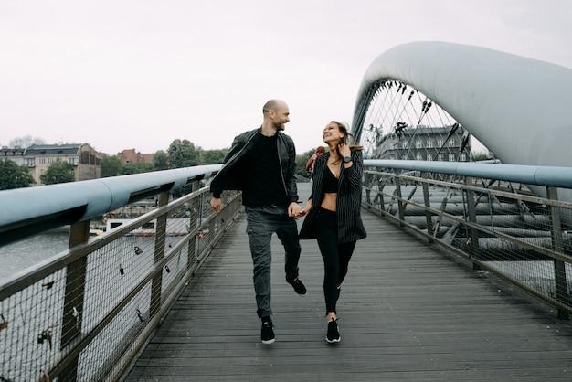 Historia miłosna. mężczyzna i kobieta w pobliżu mostu. związek miłosny. jesienny zachód słońca.