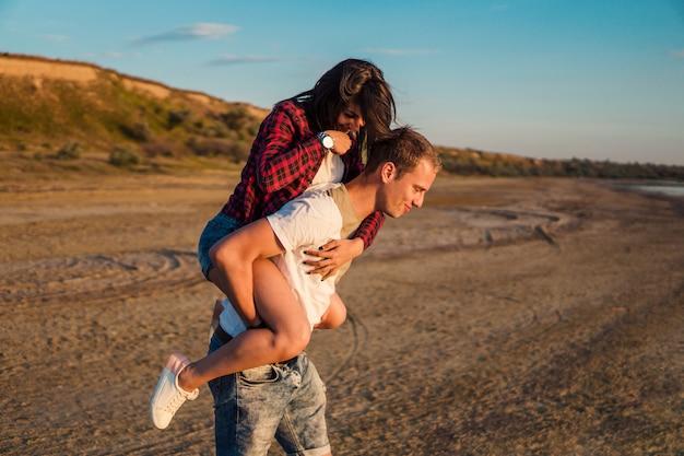 Historia miłosna młodej pięknej pary piggybacking na plaży o zachodzie słońca