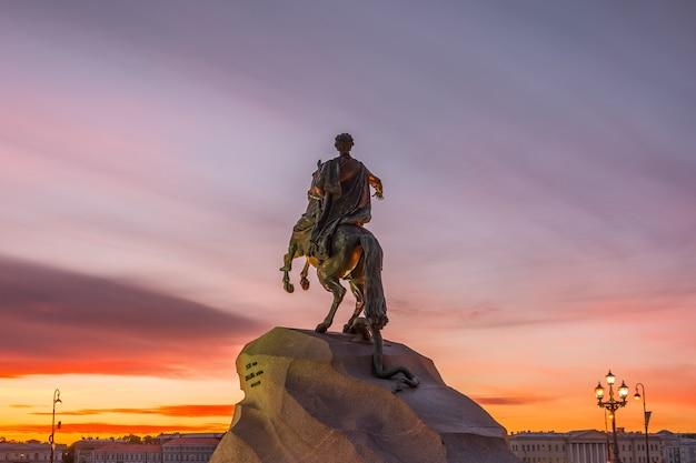 Historyczna statua pomnika piotra 1, brązowy jeździec w sankt-petersburgu na zachód wieczorem niebo.