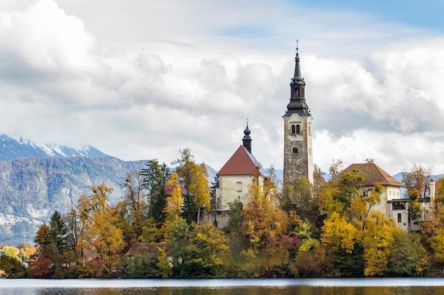 Historyczny kasztel otaczający zielonymi drzewami blisko jeziora pod białymi chmurami w krwawiący, slovenia