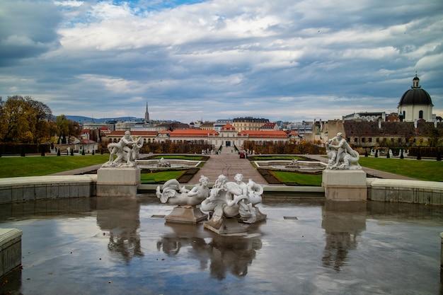 Historyczny krajobraz fontanny ze starożytnymi rzeźbami i posągami w stylu barokowym przed schloss belvedere palace w vienne, austria na tle zachmurzonego jesiennego nieba.