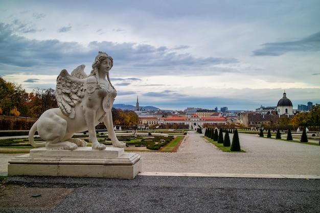Historyczny krajobraz z marmurową rzeźbą kobieta sfinks na parapecie schloss belvedere palace w wiedniu, austria na tle szarego pochmurnego nieba w jesienny dzień.