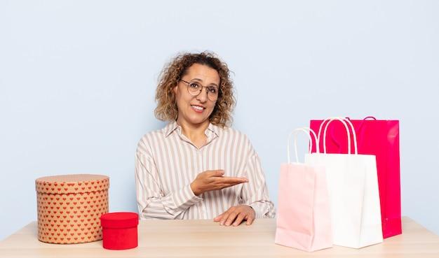 Hiszpanie kobieta w średnim wieku uśmiecha się radośnie, czuje się szczęśliwy i pokazuje koncepcję w przestrzeni kopii z dłoni
