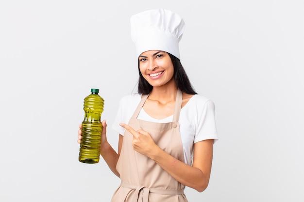 Hiszpanie ładna kucharz kobieta trzyma butelkę oliwy z oliwek.