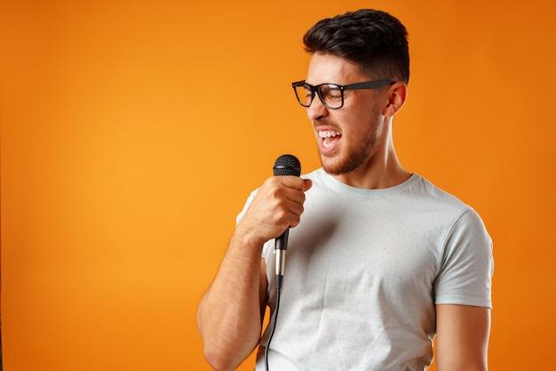 Hiszpanie młody przystojny mężczyzna śpiewa z radością w mikrofonie na białym tle