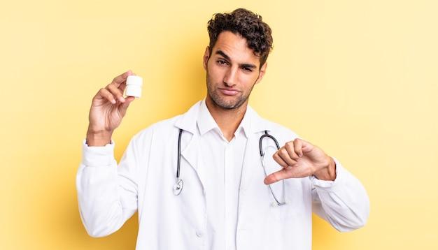 Hiszpanie przystojny mężczyzna czuje się krzyż, pokazując kciuk w dół. koncepcja pigułek na butelki lekarza