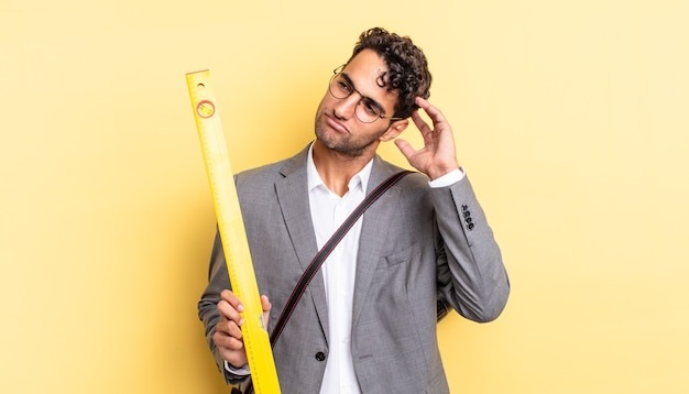 Hiszpanie przystojny mężczyzna czuje się zakłopotany i zdezorientowany, drapiąc się po głowie. koncepcja architekta