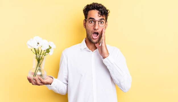 Hiszpanie przystojny mężczyzna czuje się zszokowany i przestraszony. koncepcja doniczki z kwiatami